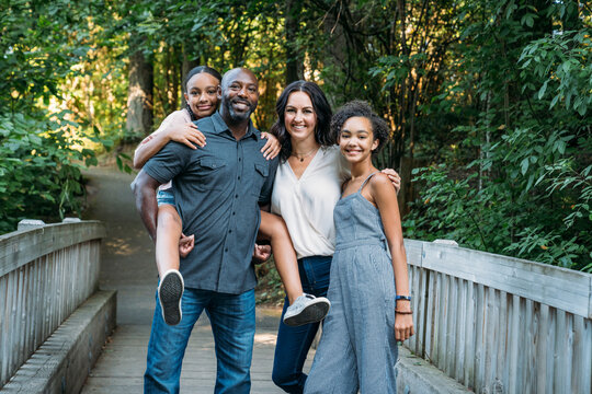 Portrait of happy mixed race family on bridge in nature park