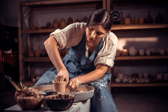 Charming craftsman works with clay on a potter's wheel. The concept of craft creativity.