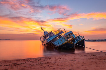Older shipwreck or abandon transportation boat parking on beach with beautiful sunset and twilight sky.