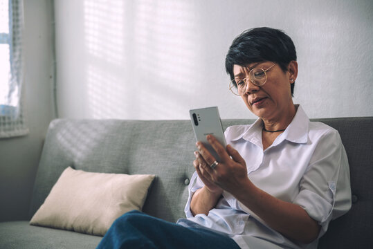 Unhappy Middle-aged gray-haired Asian woman has questions while sitting alone texting on the mobile phone or shopping online. A retired woman on the sofa at home. And senior retired Concept