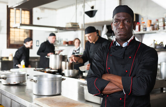 Dissatisfied african american male chef in kitchen of restaurant. High quality photo