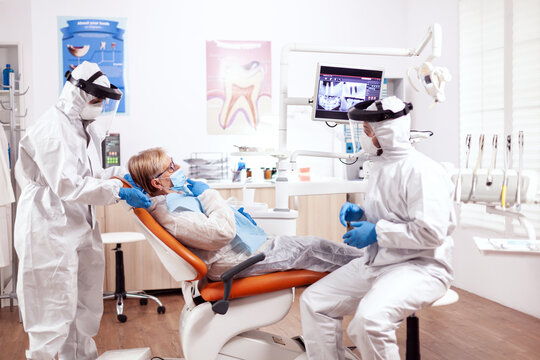 Dentist wearing equipment agasint coronavirus dicussing about teeth hygiene with senior patient. Elderly woman in protective uniform during medical examination in dental clinic.