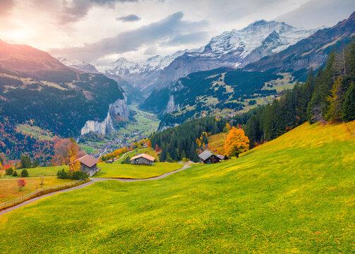 View from flying drone of Wengen village, district of Lauterbrunnen. Great sunrise scene of Swiss Alps. Astonishing autumn landscape of Switzerland countryside, Europe.