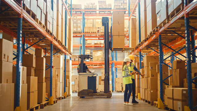 Retail Warehouse full of Shelves with Goods in Cardboard Boxes, Male and Female Supervisors Use Digital Tablet Discuss Product Delivery while Scanning Packages Forklift Working in Logistics Storehouse