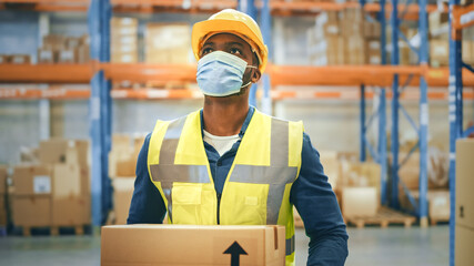 Portrait of Handsome Male Worker Wearing Medical Face Mask and Hard Hat Carries Cardboard Box Walks...