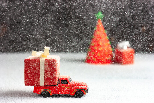 The car delivers a gift, cargo in a strong snowstorm. New Year card. Spirit is born