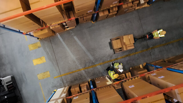 Top-Down View: Worker Moves Cardboard Boxes using Hand Pallet Truck, Walking between Rows of Shelves with Goods in Retail Warehouse. People Work in Product Distribution Logistics Center