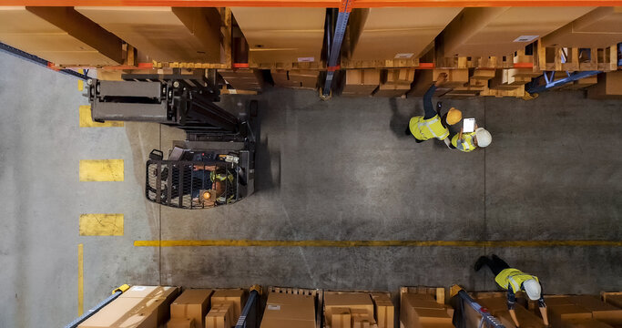 Top-Down Shot: Electric Forklift Truck Operator Lifts Pallet with Cardboard Box of in a Big Retail Warehouse a Shelf. Logistics Product and Goods Delivery and Distribution Center
