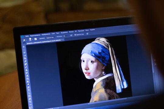 New York, USA - 9 April 2020: Adobe Photoshop on laptop screen close up. Man designer using application on display, blurry background, Illustrative Editorial