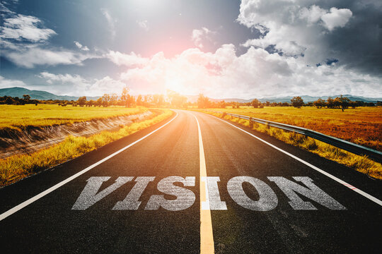 vision written on highway road in the middle of empty asphalt road and beautiful blue sky. Concept for vision future.
