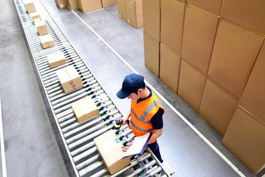 Mann scannt Pakete für den Versand im Versandhandel ein - Fliessband mit Paketen // Man scans parcels for mail order dispatch - assembly line with parcels