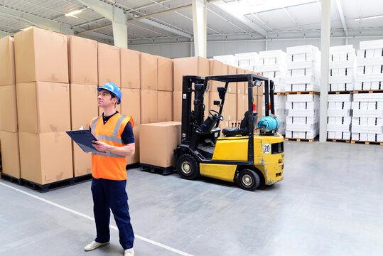 Mann arbeitet im Lagerhaus einer Spedition, im Hintergrund Gabelstapler - Industriehalle // Man works in the warehouse of a forwarding agency, in the background forklift trucks - industrial hall