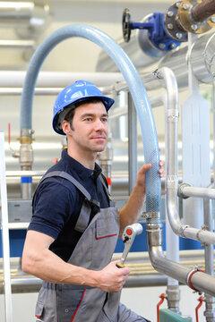 Monteur im Anlagenbau in der Industrie - Arbeitskleidung mit Helm und Werkszeug - Arbeitssicherheit // Fitter in plant construction in industry - Work clothing with helmet and tools - Work safety