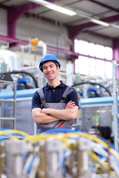 Portrait junger freundlicher Arbeiter in einer Industrieanlage - Arbeitsplatz Industrie // Portrait of young friendly worker in an industrial plant - Workplace Industry