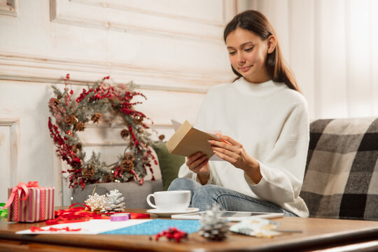 Woman opening, recieving greeting card for New Year and Christmas 2021 from friends or family. Reading a letter with best wishes, looks happy, cheerful, smiling, opening envelope. Holidays