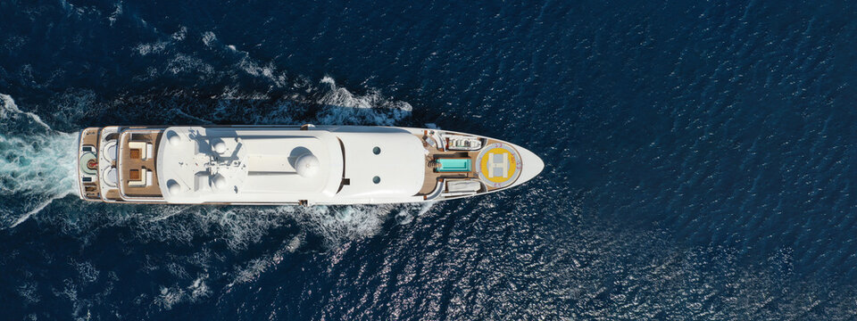 Aerial drone ultra wide photo of luxury yacht with wooden deck anchored in tropical exotic island bay wit turquoise sea