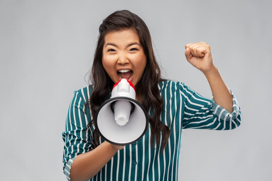 communication, feminism and people concept - angry young asian woman with pierced nose speaking to megaphone over grey background