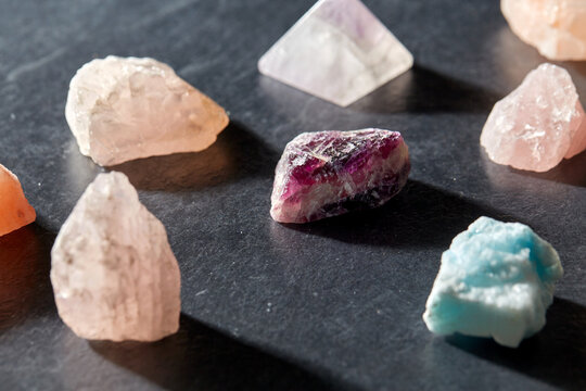 occult science, minerals and geology concept - quartz crystals and gem stones on slate background