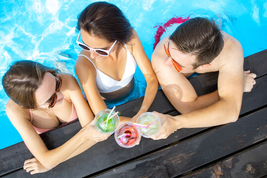 Happy friends enjoying in pool bar. Summer beach party. Drinking tropical alcohol cocktails. Top view of girls and boy communicated in pool bar.