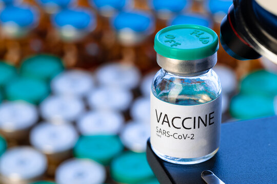 Vial of Covid-19 vaccine next to a microscope