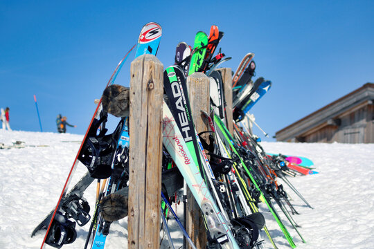 Skis, snowboards and ski sticks hanged to a ski & snowboard rack on a sunny day in Chamonix, France - March 13 2017.
