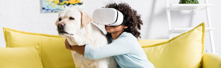 African american girl in vr headset embracing dog, while sitting on yellow sofa at home, banner