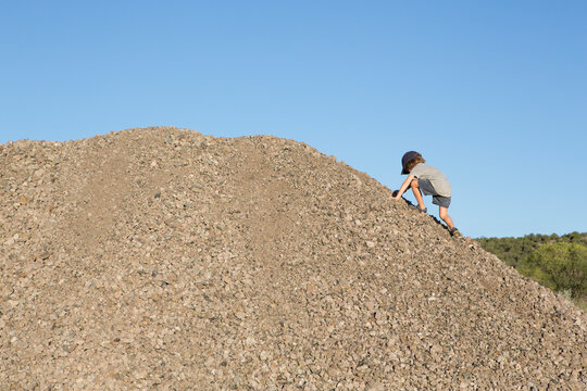 4 year old boy climbing a gravel hill