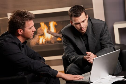 Businessmen working together at fireplace, getting financial advice, looking at laptop computer.