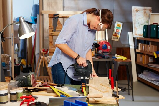 Woman working in workshop, using top handle jigsaw.