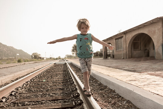 4 year old boy balancing on railroad track, Lamy, New Mexico.