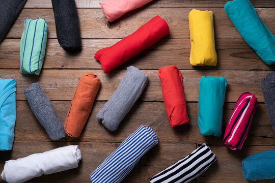 close up of rolled colorful t shirt clothes on wooden table background