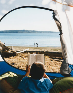 Young boy reading book at the opening of a tent on the beach.