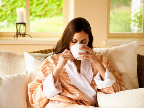 Close up of woman in bathrobe drinking tea at a luxury spa