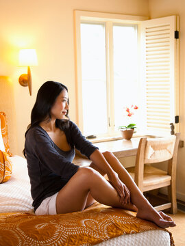 Asian woman relaxing on bed