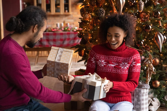 Overjoyed young African American man and woman giving Christmas gift boxes, presents, sitting on floor near decorated festive tree, family celebrating New Year at home, enjoying winter holidays