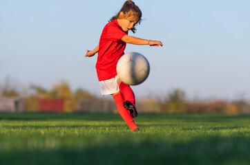 Little girl kicks soccer ball