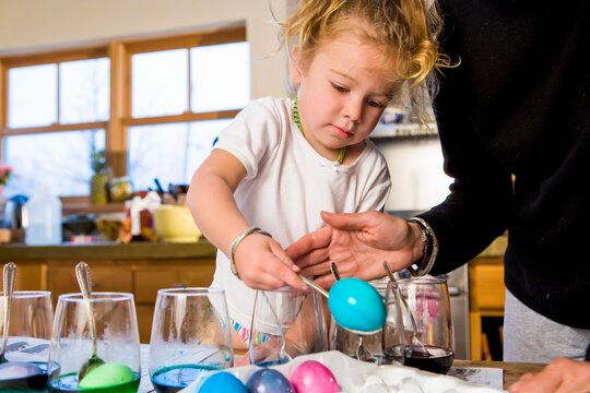 3 year old girl coloring easter eggs at home with her mother