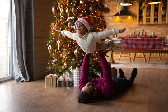 Loving African American father playing funny game with adorable little son wearing red cap, family celebrating Christmas at home, dad lying on floor near tree, carrying boy pretending flying