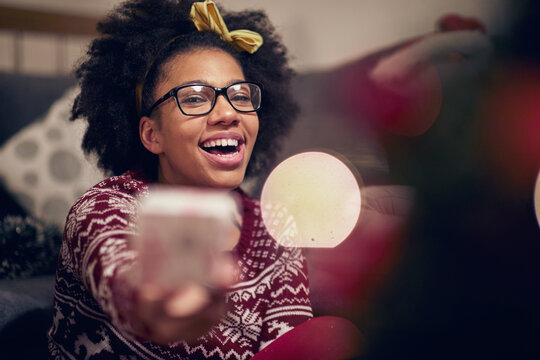 Cheerful afro american teenage girl reciving present; Happy family moments concept