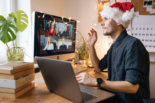 Christmas day remote celebration. Young man having Zoom video call via a computer in the home office. Stay at home and work from home concept during Coronavirus pandemic.