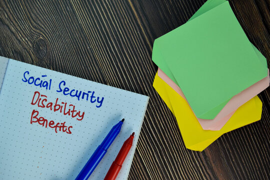 Social Security Disability Benefits write on sticky note isolated on Wooden Table. Business concept