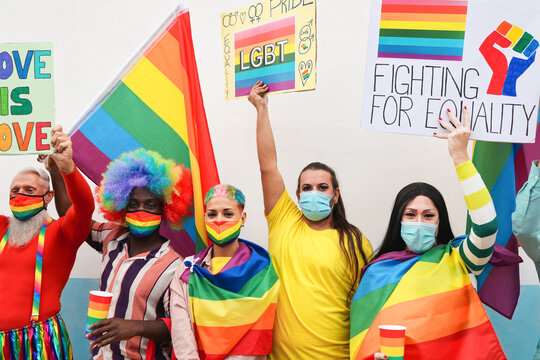 Mutiracial people protest at gay pride party with banners and lgbt rainbow flags wearing protective face mask - Homosexual and coronavirus lifestyle concept - Main focus on black man face
