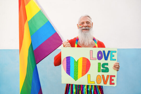 Hipster senior man at gay pride holding rainbow flag and lgbt banner - Focus on face