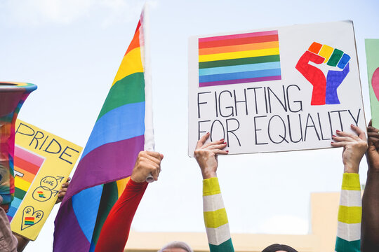 Banners and lgbt rainbow flags at gay pride event outdoor - People protest for equality rights concept - Focus on right white hands
