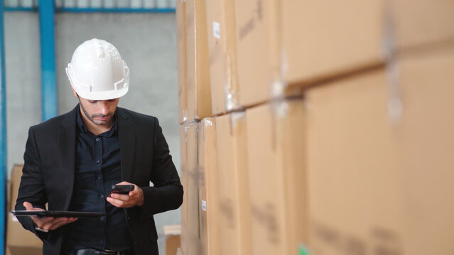 Factory manager using tablet computer in warehouse or factory . Industry and supply chain management concept .