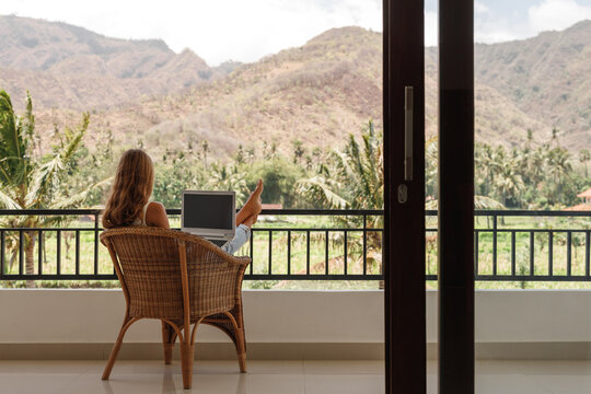 Back view happy confident woman using laptop while sitting on balcony and working from home