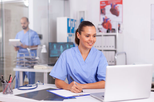 Smiling nurse using laptop computer and writing notes on clipboard in hospital office with doctor in the background. Health care physician using computer in modern clinic looking at monitor,