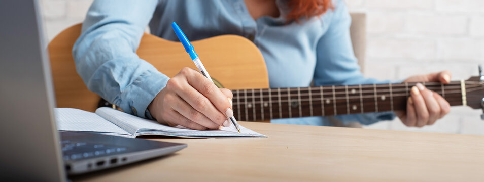 A woman with a guitar writes notes in a notebook. The girl composes a song
