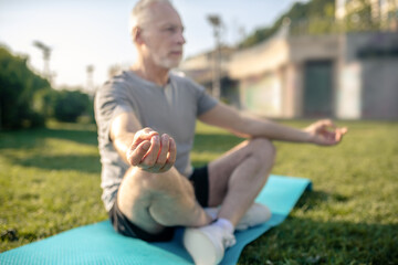 Grey-haired male sitting in lotus pose with hands in Gyan mudra