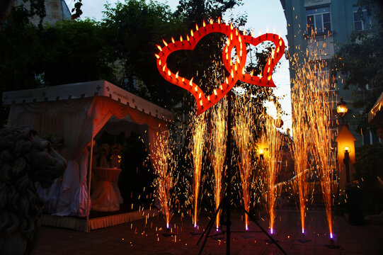 Romantic heart-shaped firework at local backyard wedding party with two glowing hearts / event entertainment. Festive fire show for celebrating.